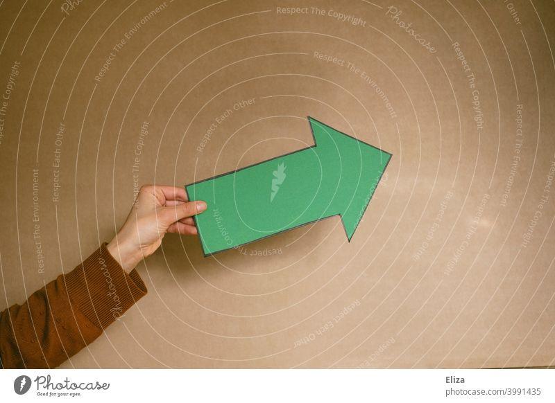 Hand hält einen grünen Pfeil. Richtung und Orientierung. richtungsweisend Empfehlung Wegweiser positiv Zukunft da lang