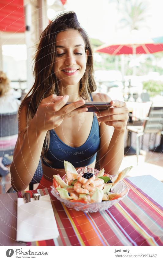 Junge Frau, die ihren Salat mit einem Smartphone fotografiert, während sie in einem Restaurant sitzt Lebensmittel Salatbeilage Gesundheit Telefon Mobile