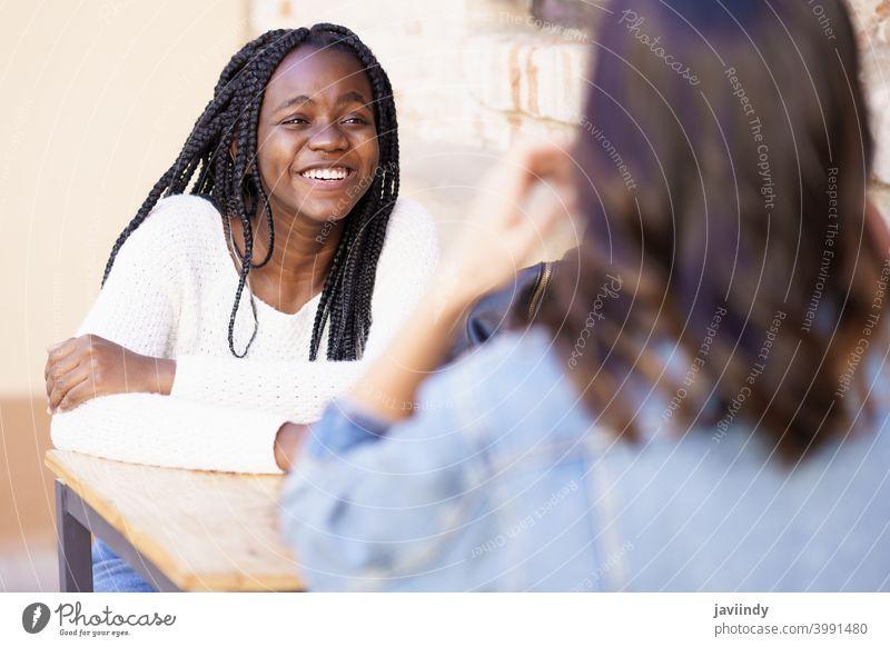 Zwei multiethnische Freunde unterhalten sich an einem Tisch vor einer Bar. Frau im Freien rassenübergreifend Fröhlichkeit Mädchen Freundschaft Glück Lächeln