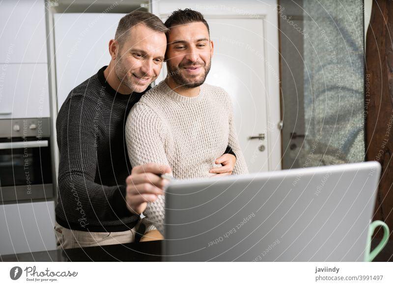 Romantisches Gay-Paar, das gemeinsam zu Hause mit ihren Laptops arbeitet. schwul Männer Telearbeit Umarmung Homosexualität umarmend lgbt lgbtq männlich