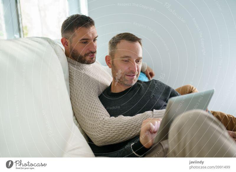 Schwules Paar, das seine Reisepläne gemeinsam mit einem digitalen Tablet berät. schwul Männer Homosexualität lgbt Tablette lgbtq männlich Partnerschaft Freund