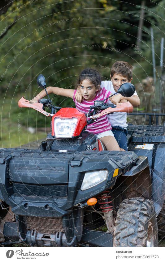 Zwei kleine Kinder fahren auf einem Quad aktiv Aktivität Abenteuer Fahrrad Junge Bruder PKW Kindheit Laufwerk Fahrer Emotion Freiheit Freundschaft Spaß Spiel