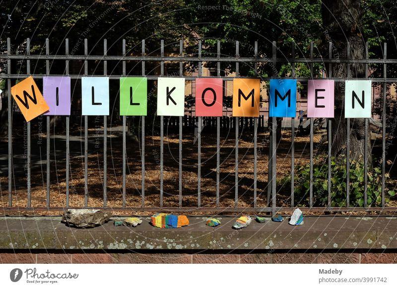Schriftzug WILLKOMMEN aus schwarzen Buchstaben auf buntem Papier auf dem Zaun einer Schule nach den Sommerferien im Nordend in Frankfurt am Main in Hessen