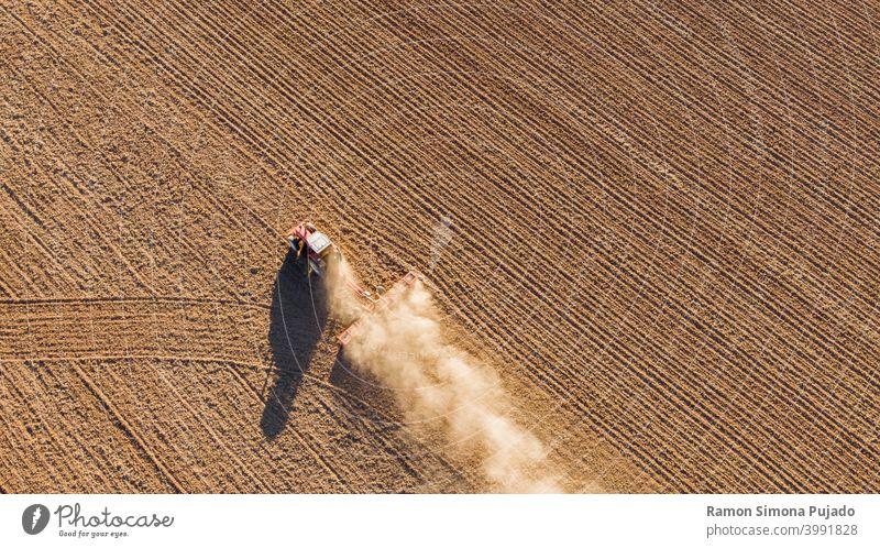 Drohnenansicht eines Traktors, der das Land bearbeitet Ansicht von oben Traktoren braun Landwirtschaft Bauernhof Landwirtschaftliche Geräte Bereiche Feld