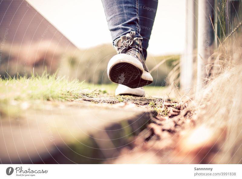 Fröhlich in Turnschuhen laufend auf einer Bahnschwelle Schuhe Sommer Spaziergang Fröhlichkeit Fuß Fußgänger Chucks Natur rennen Leichtigkeit Gute Laune draußen