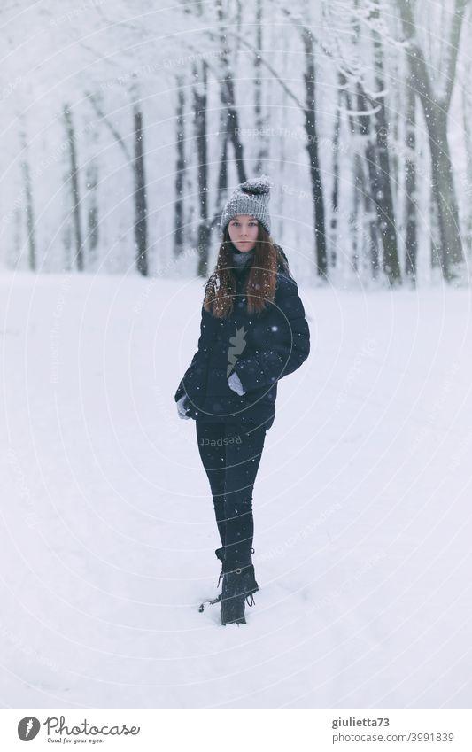 Porträt eines Teenager Mädchens im Winter bei Schneefall stehend in einem verschneiten Park Vorderansicht Blick in die Kamera Farbfoto Jugendliche Außenaufnahme