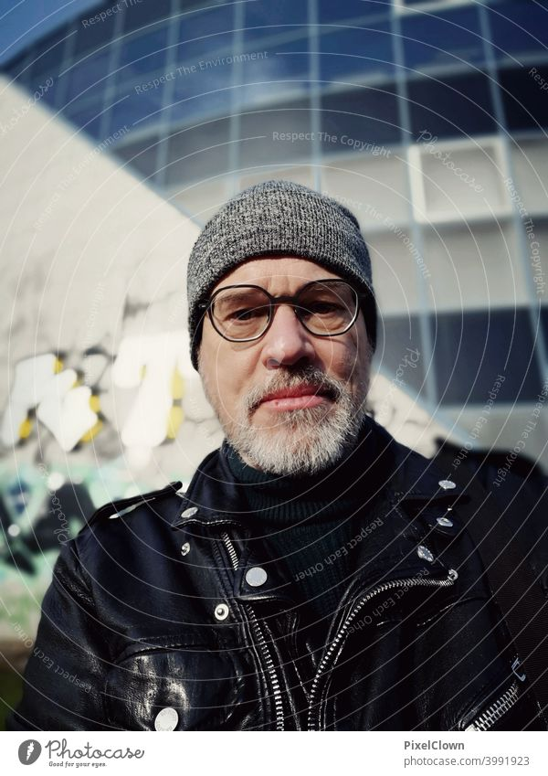 Mann mit Brille und Mütze vor einem Gebäude Ein Mann allein Porträt 1 Mensch Erwachsene Männergesicht Gesicht Kopf Bart