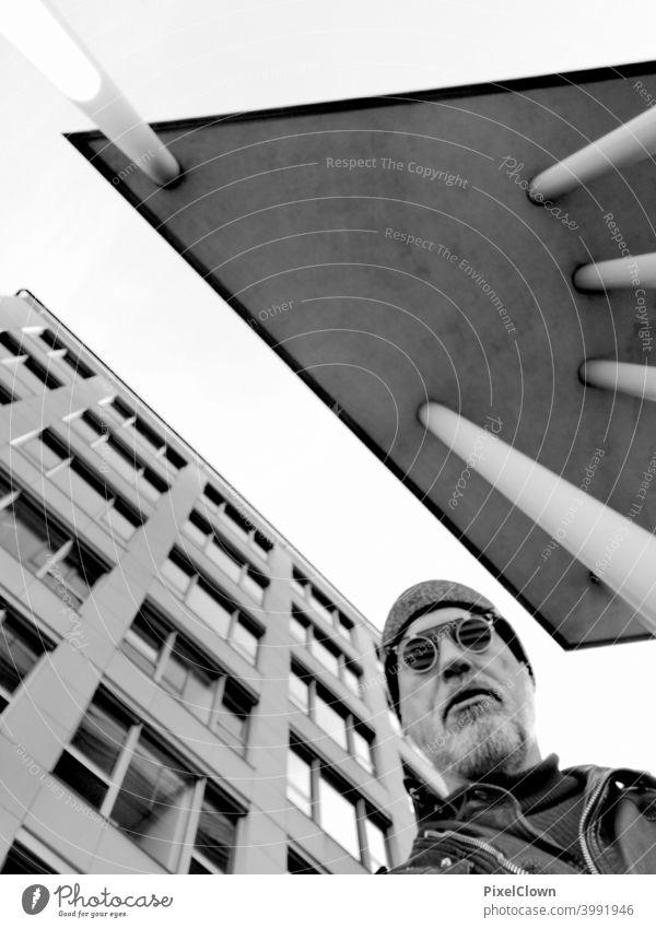 Ein alter Mann steht zwischen zwei Hochhäusern und schaut in den Himmel Gesicht Brille Blick Bart Kopf Porträt Architektur Gebäude Großstadt