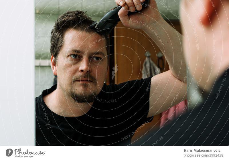 Mann selbst Haarschnitt auf dem Spiegel im Bad Accessoire Friseur Pflege Schermaschine Coronavirus Bund 19 geschnitten Gerät Gesicht Mode Typ Behaarung