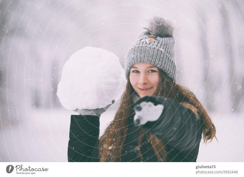 Glückliches, freches Teenager Mädchen im Winter mit riesengroßem Schneeball weiß Bommelmütze feminin Gedeckte Farben Schneeflocken verschneit langhaarig