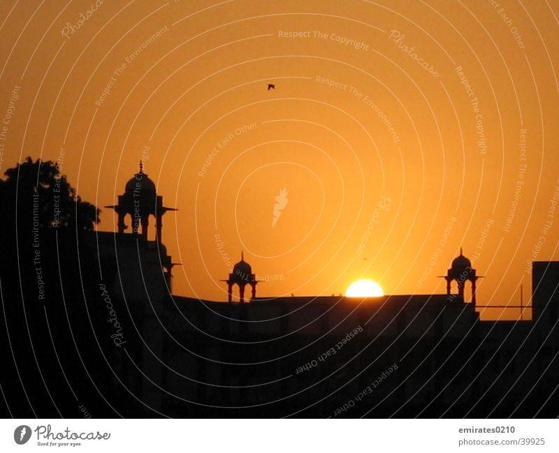 disappearing sun Sonne schwarz gelb Farbe Gebäude orange Turm Indien