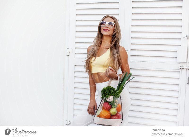 Ein junges Mädchen mit Sonnenbrille und Sportkleidung steht im Hintergrund der Tür mit einer Tüte voller Gemüse und Obst. Das Konzept der gesunden Ernährung und des gesunden Lebensstils