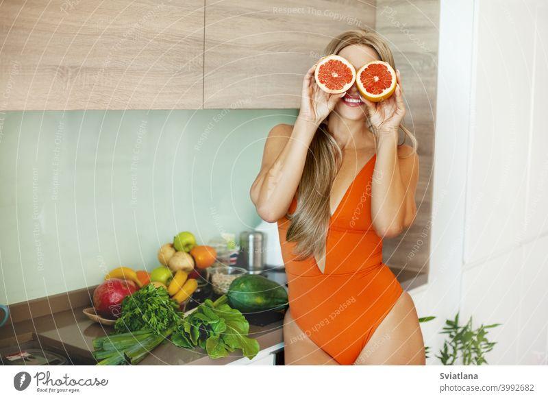 Porträt eines sportlichen Mädchens mit einer Grapefruit in ihren Händen in der Küche mit frischem Gemüse und Obst. Das Konzept eines gesunden Lebensstils, Gesundheit, Schönheit