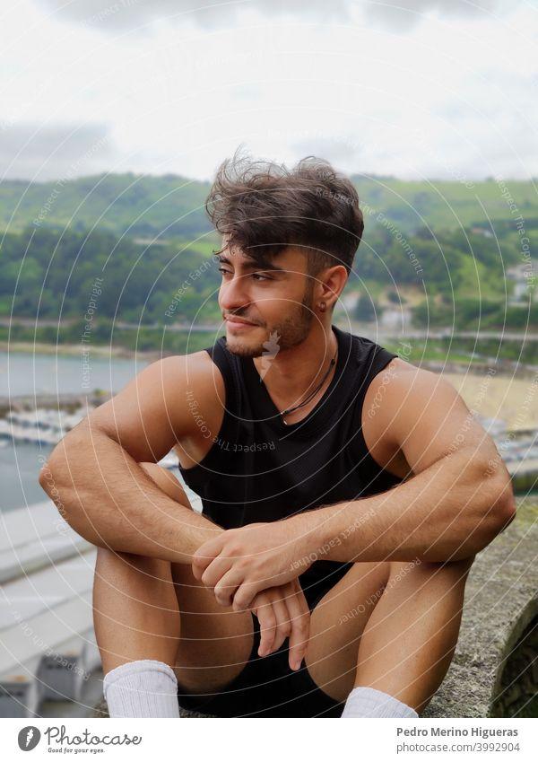 Hispanischer Mann sitzend, posierend, mit verblasstem Haar und Bär, der ein Basketball-T-Shirt trägt Model kein Blick jung schön Korb-T-Shirt Erwachsener