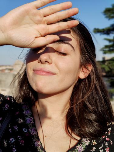Mädchen mit geschlossenen Augen, das mit der Hand die Sonne abdeckt. Gesundheit Dermatologie Frau Behandlung beunruhigt Sonnenschein heiß Gesichtsbehandlung