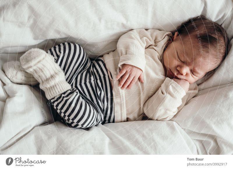 Prokrastination - Baby liegt zusammen gekuschelt auf Bettdecke mit verschränkten Beinen und der Hand unterm Kinn da und schläft schlafen friedlich träumen