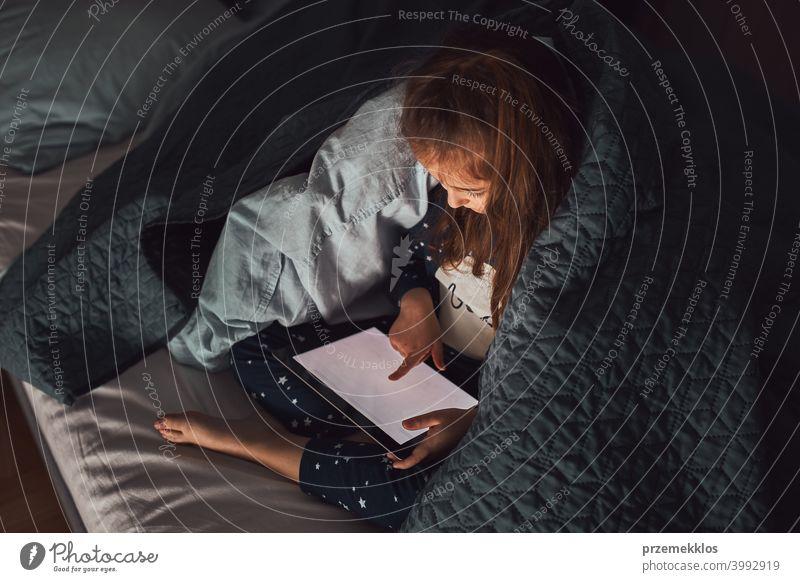 Kleines Mädchen mit Spaß beobachten, spielen und hören Geschichten auf Tablet-Computer liegen unter Bettdecke Nacht Schlafenszeit Kind heimwärts Schlafzimmer