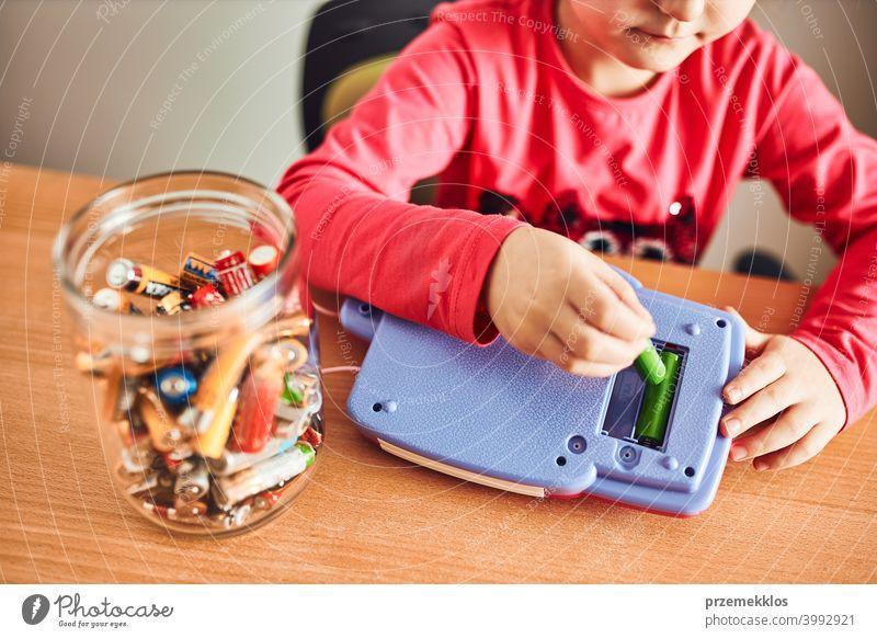 Kleines Mädchen, das verbrauchte Batterien aus einem Spielzeug entfernt und in ein Gefäß zum Recycling legt Behälter Kind sammelnd Konzept konzeptionell