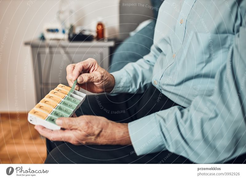 Älterer männlicher Patient beim Öffnen des Tablettenspenders zur Einnahme der nächsten Medikamentendosis. Organisieren von Medikamenten geduldig Person