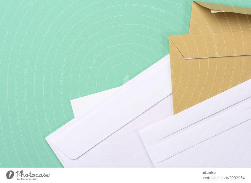 leere weißes Papier braun und weiß Umschläge auf einem grünen Hintergrund Kuvert Brief blanko Nachricht Büro Beitrag Postkarte Schriftstück Porto