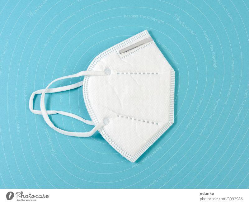 weiße medizinische Einwegmaske auf blauem Hintergrund, persönliche Schutzausrüstung für die Atemwege vor viralen Infektionen Mundschutz Medizin Pandemie