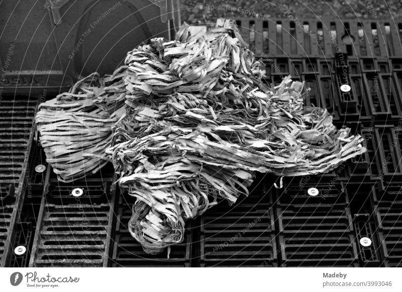 Papierknäuel aus Papierstreifen auf gerasterten Paletten auf einer Baustelle in der Hauptstadt Berlin, fotografiert in klassischem Schwarzweiß Abfall Müll
