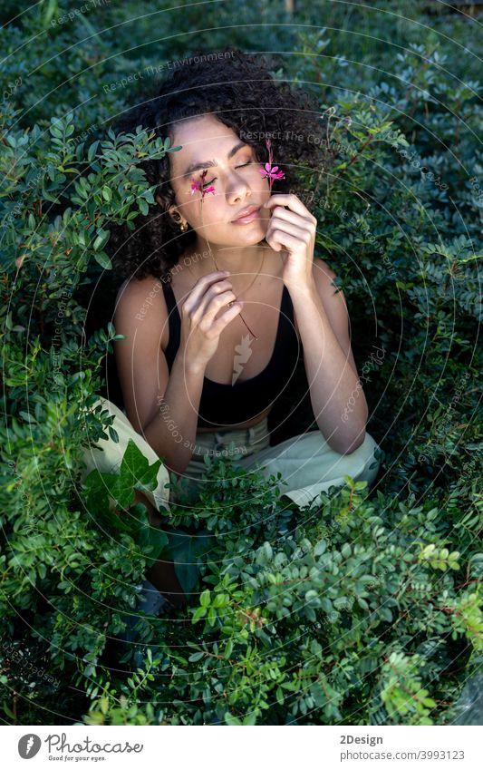 Outdoor-Mode Foto von schönen jungen Frau von Pflanzen umgeben Blume Schönheit Sommer lockig Mädchen Porträt Gesicht Behaarung Model niedlich Lifestyle