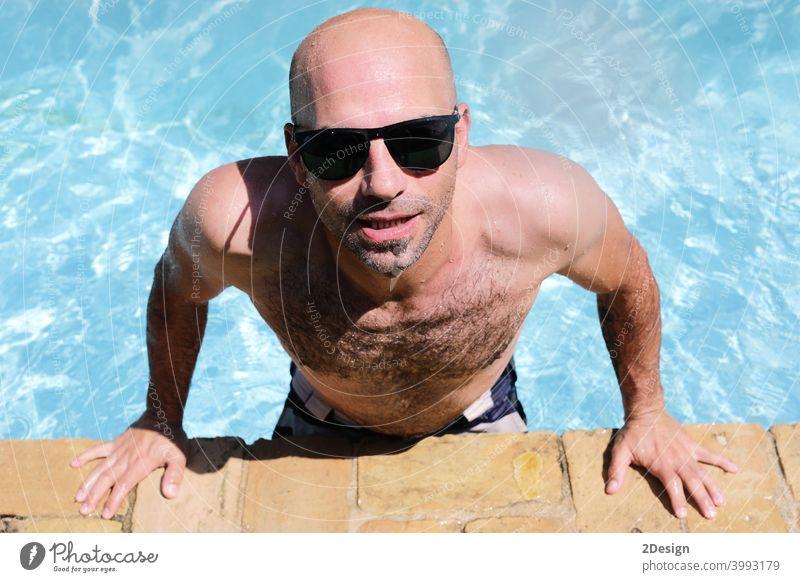 gut aussehend Kerl halb nackt fröhlich Mann lächelnd lachend in blauem Wasser Schwimmbad nass Bräune Schwimmsport Pool kahl Sonnenbrille Sommer jung Glück