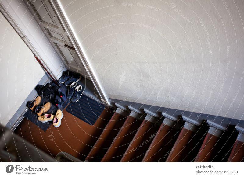 Schuhe vor der Wohnungstür absatz abstieg abwärts altbau aufstieg aufwärts besuch fenster geländer haus mehrfamilienhaus menschenleer mietshaus party schuhe