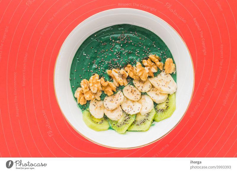 Spirulina-Smoothie-Schale mit Banane, Walnüssen, Kiwi- und Chiasamen auf rotem Hintergrund Antioxidans Schalen & Schüsseln Frühstück Nahaufnahme Farbe lecker