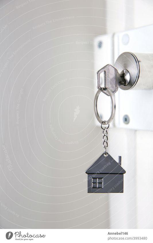 Silberner Hausschlüssel in weißer Tür, mit kleinem Schlüsselanhänger Haus, öffnende Tür zu neuem Haus, Heim, Investition, Immobilienkonzept, Platz für Text