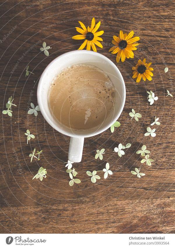 Es gibt Cappuccino zum Frühstück...  Der Holztisch ist liebevoll mit weißen und gelben Streublümchen dekoriert Kaffee Café Tasse Getränk heiß Morgen Koffein