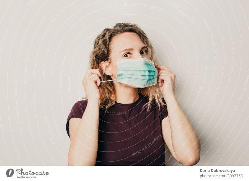 Mädchen setzt eine medizinische Maske auf Medizin Gesundheit Coronavirus Schutz Frau Pflege Person Hintergrund blau Arzt Operationsmaske Gesichtsmaske