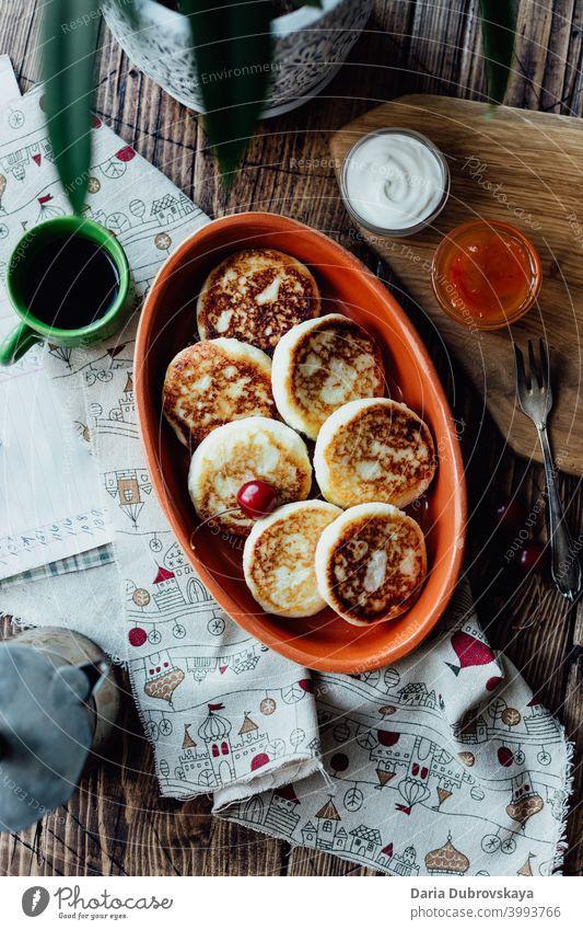 Hüttenkäse-Pfannkuchen auf einem Holztisch süß Frühstück hölzern Speise Dessert traditionell Tisch Cottage Käse Teller Quark Molkerei gebraten Mahlzeit Morgen