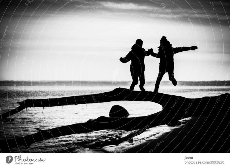 Gemeinsam schaffen wir das, lass uns einfach an die Hände fassen | Zwei Kinder springen am Ufer des Meeres von einem umgefallenen Baumstamm herunter | starker Kontrast in schwarzweiß, so dass kaum mehr als die Silhouette zu sehen ist