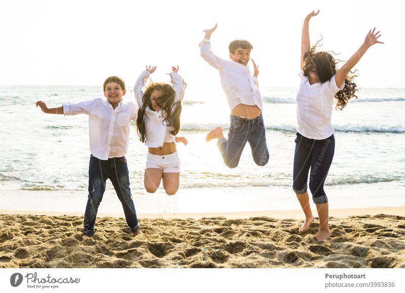 Glückliche Kinder springen zusammen am Strand springend MEER Menschen Familie Wasser Sommer Himmel Sonnenlicht Menschengruppe Sonnenuntergang Urlaub reisen
