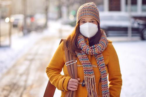 Brünette Frau mittleren Alters in Winterkleidung mit Gesichtsmaske im Freien aufgrund des Corona-Virus auf dem Weg zur Arbeit brünett Mundschutz ffp2 Schutz