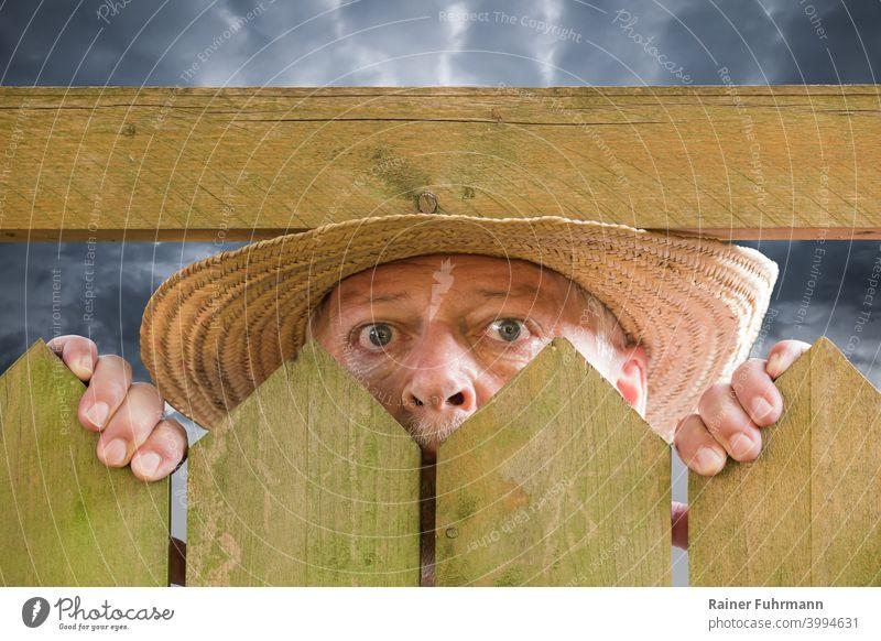 Ein neugieriger Mann schaut über einen Gartenzaun. Er trägt einen Strohhut. Im Hintergrund sind Gewitterwolken zu sehen. Nachbar Neugier spionieren Stalker