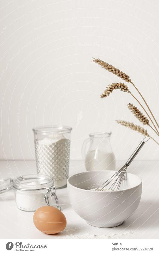 Mehl in einer Schüssel und Backzutaten auf einem weißen Tisch Zutaten backen Ei weißer Hintergrund Weizenähre Küche Vorbereitung roh Essen zubereiten frisch