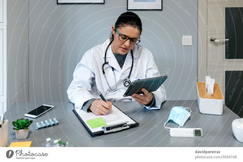 Weiblicher Arzt bei der Online-Konsultation mit der Tablette Telemedizin medtech medizinische Online-Dienste Frau arbeiten schreibend Videoanruf