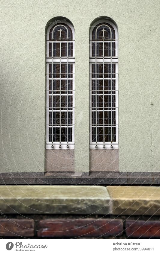 blick über die klostermauer auf zwei vergitterte kapellenfenster fenstergitter kreuz kreuze klosterfenster kirchenfenster klosterkapelle sicher sicherheit