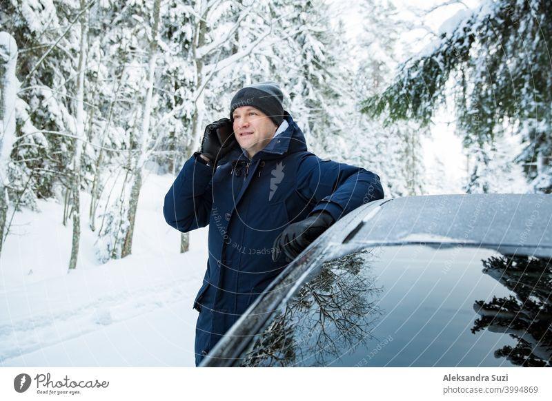 Mann in warmer Winterkleidung steht am Auto, mit Telefon. Snowy Winter Landstraße, Auto mit Eis bedeckt, Schöne Wald unter dem Schnee. Hilfsbereitschaft Anruf