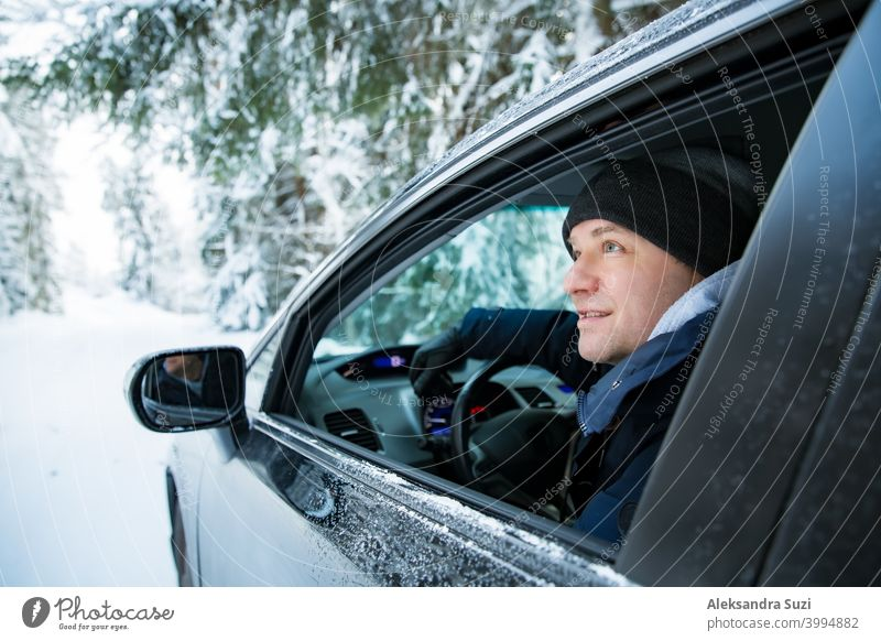 Mann in warmer Winterkleidung sitzt im Auto. Snowy Winter Landstraße, Auto mit Eis bedeckt, Schöne Wald unter dem Schnee. Schneesturm PKW kalt Arbeitsweg