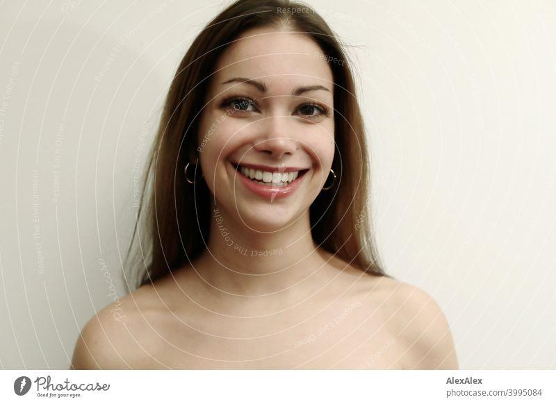 Porträt einer jungen, schönen, brünetten Frau die lächelt vor einer hellen Wand Junge Frau hübsch langhaarig schlank Teenager 18-25 Jahre Jugendliche ästhetisch