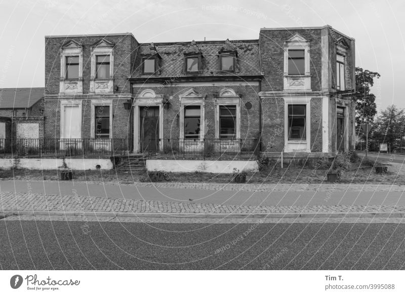 ein altes kaputtes Haus an der Straße in Brandenburg s/w b/w Fenster Schwarzweißfoto ruhig Einsamkeit Architektur b&w Außenaufnahme dunkel Ruine Dorf Gebäude