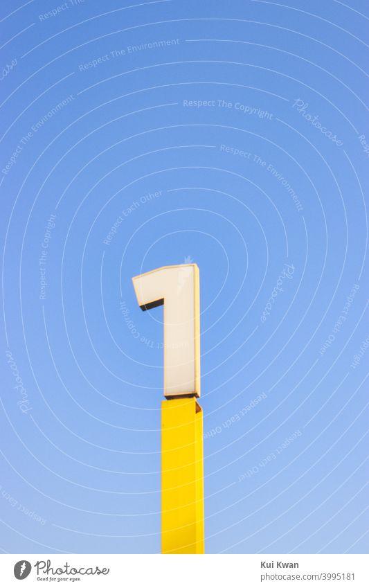 Nummer 1 ; Nummer-Eins-Zeichen in Gelb ; mit einfarbig blauem Himmel eine gelb zählen Nummer eins Ziffern & Zahlen Schriftzeichen minimalistisch sehr wenige
