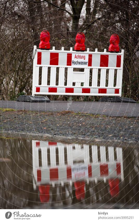 amtliche Absperrung eines Weges wegen Hochwasser. Leuchtbake mit Warnschild spiegelt sich im Wasser Überflutung Gefahr Spiegelung Sicherheit Warnhinweis