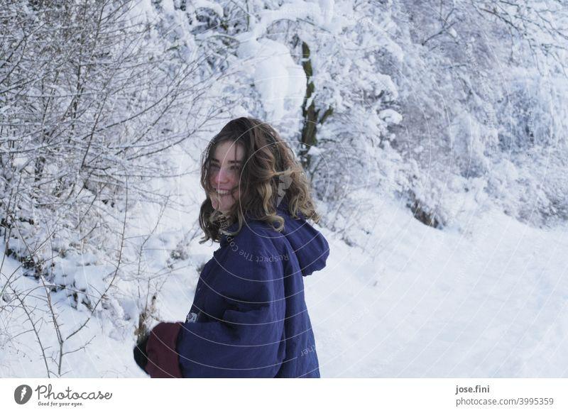 Junge Frau mit warmer Kleidung, lachend, Schnee im Hintergrund. eine Person junger Erwachsener Mädchen Jugendliche feminin Porträt hübsch frisch natürlich