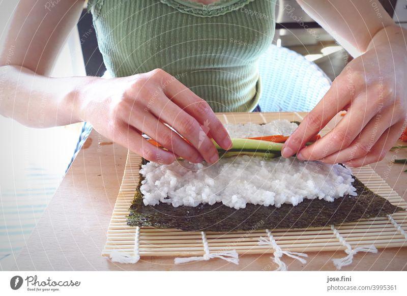 Hände einer Frau, Sushi selbst zubereitend Oberkörper Essen zubereitung Küche Reis Lachs Japanisch Asiatische Küche traditionell Wasabi Ingwer Holztisch