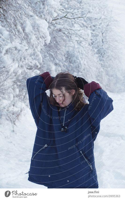 Junge Frau mit warmer Kleidung, Blick nach unten, Hände über dem Kopf, Schnee im Hintergrund. eine Person junger Erwachsener Mädchen Jugendliche feminin Porträt